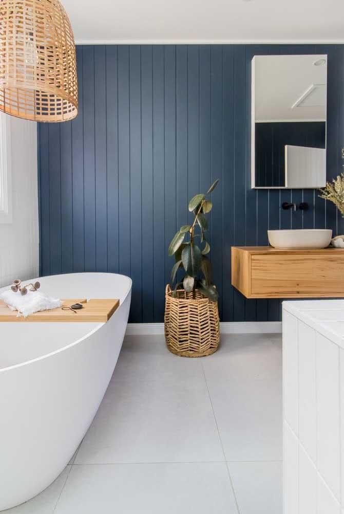 A parede de madeira também é um elemento que remete as casas situadas no litoral. Aqui neste banheiro, a madeira foi pintada de azul marinho.