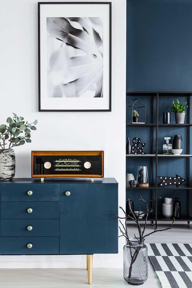 Decoração sala de estar com predominância do azul marinho: tanto na pintura da parede como no aparador da sala.