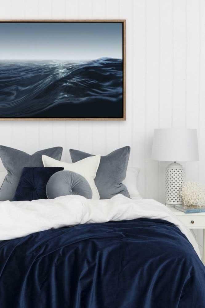 Já aqui, um belo quadro com imagem do mar e roupa de cama na cor azul.