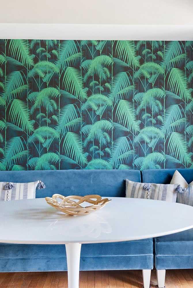 Sala de jantar com sofá de veludo azul e papel de parede das com palmeiras.