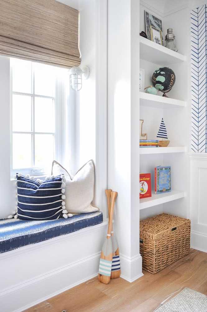 Quarto infantil com tema Navy: azul e branco presente nas almofadas, assento na janela e até no papel de parede.