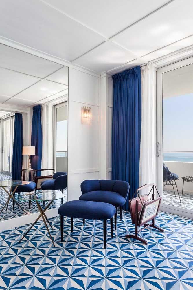 Sala luxuosa com piso geométrico em duo de azul marinho e branco. As cortinas também seguem o mesmo padrão de cores.