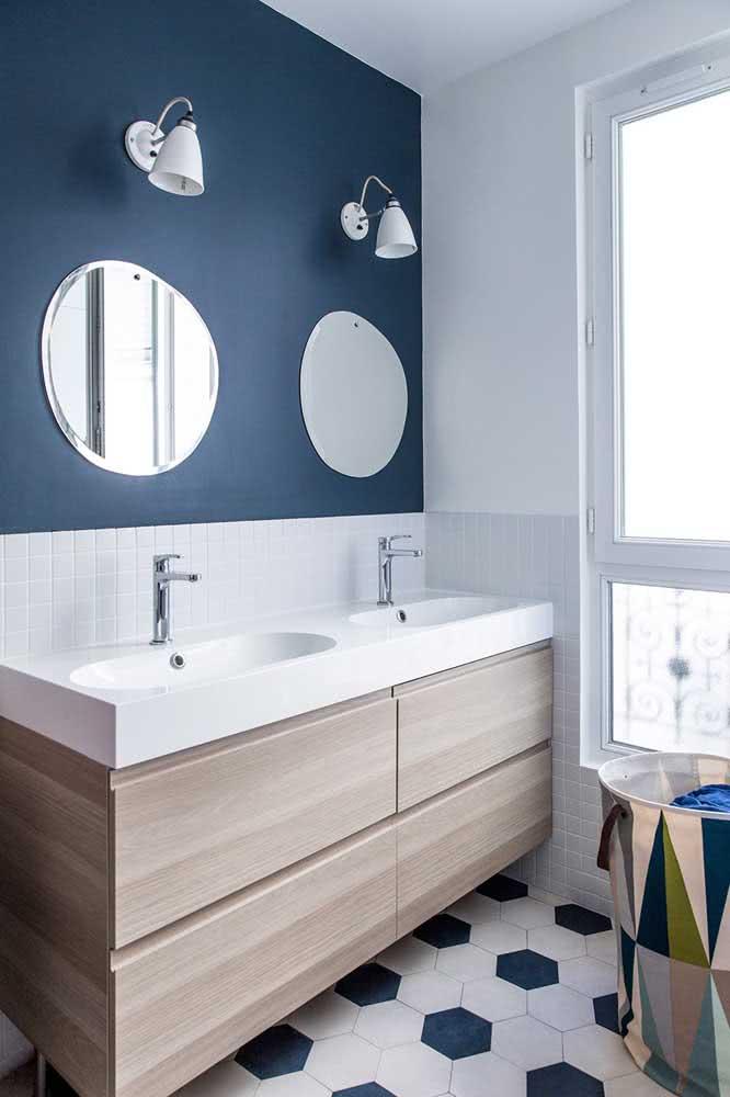 Banheiro com azulejos hexagonais em duo de branco e azul. Parede também na cor azul.