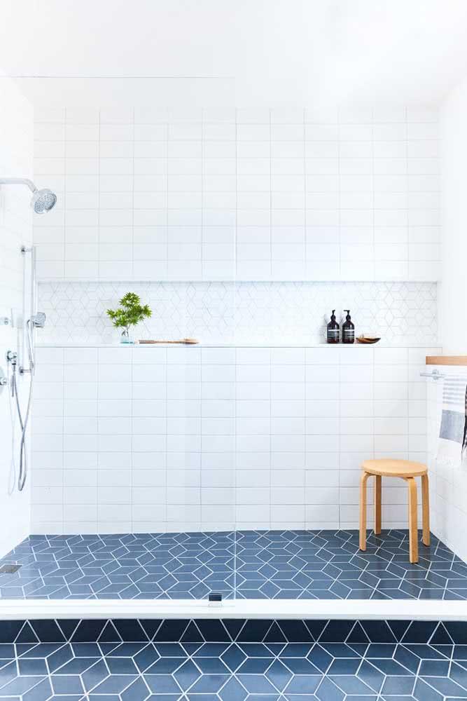 Banheiro com box com azulejos hexagonais no piso na cor azul.