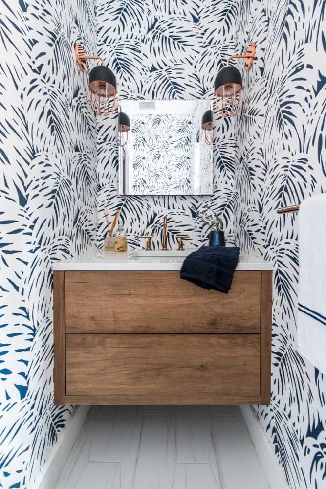Papel de parede no banheiro com ilustração de folhas de palmeiras em duo azul e branco.