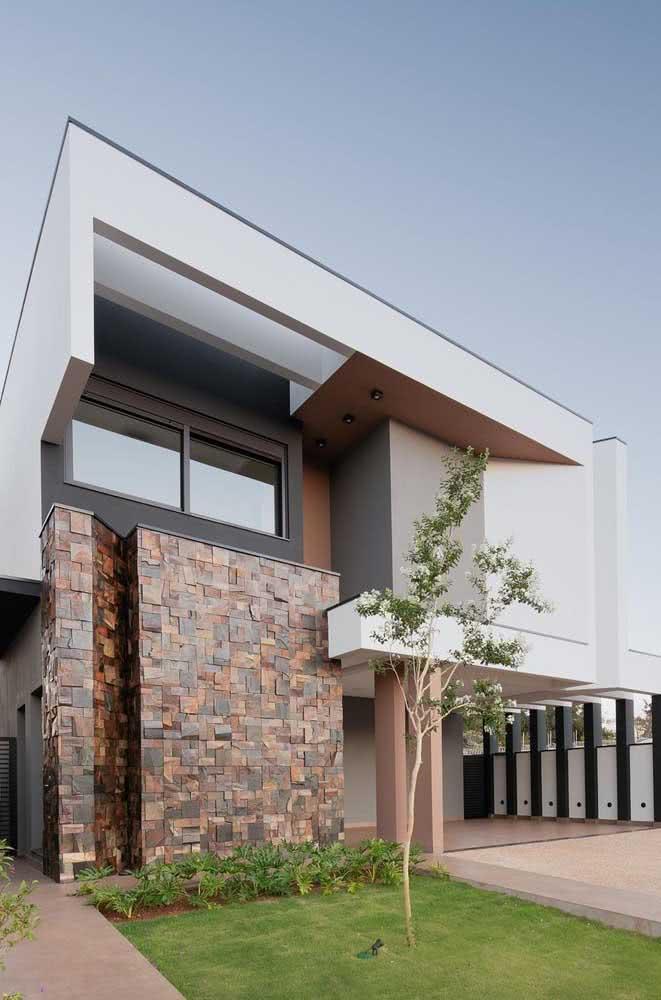 Muro de pedra ferro em formato mosaico complementando a fachada da casa com muito estilo