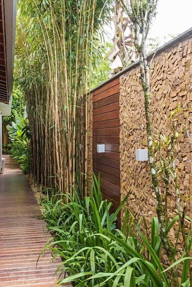 Muro de entrada em pedra portuguesa. Para combinar, portão de madeira e o verde das plantas