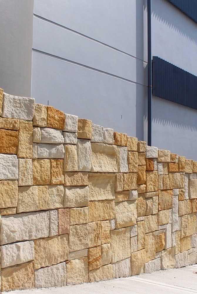 Muro de contenção de pedra madeira. Destaque para o contraste com a casa de arquitetura moderna