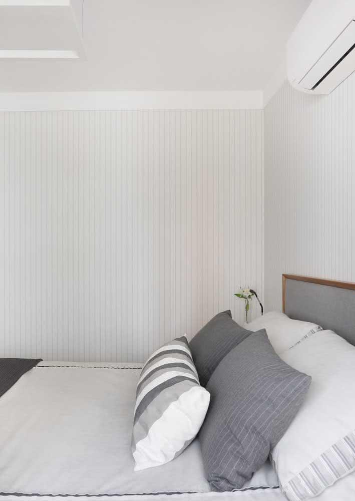 Quarto de casal com papel de parede branco listrado.