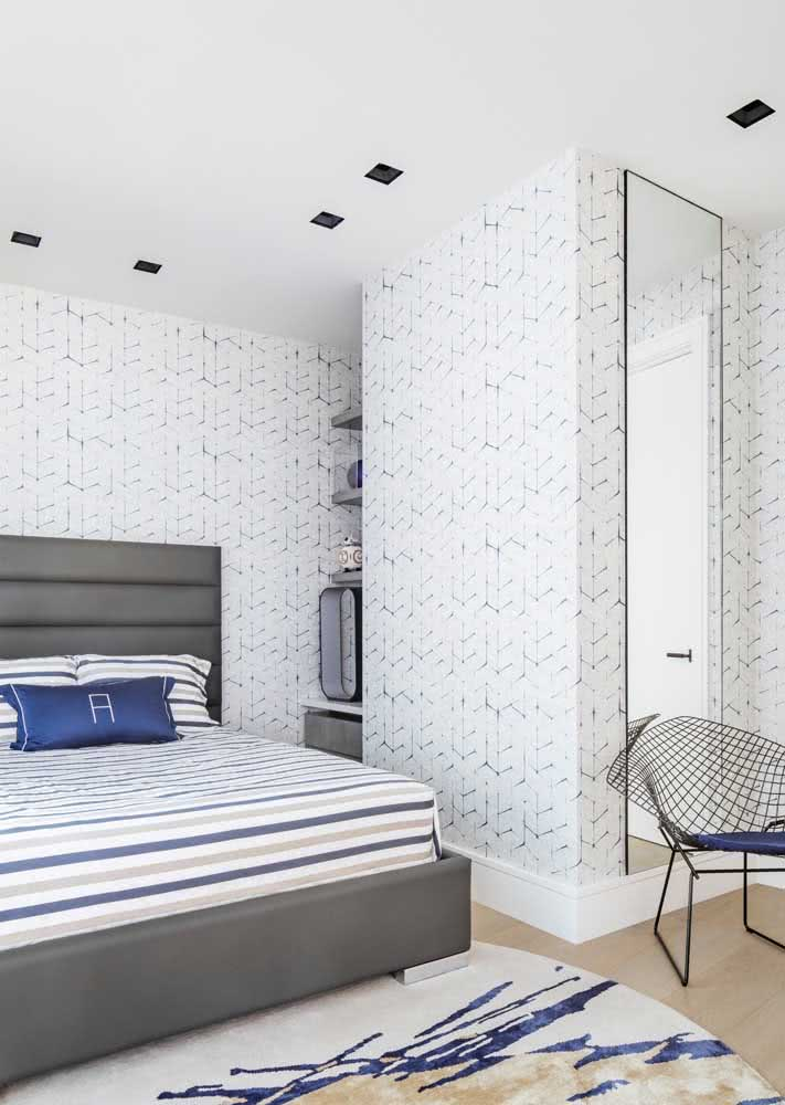 Papel de parede azul e branco com pequenos detalhes e padronagem que se repete por toda a extensão.