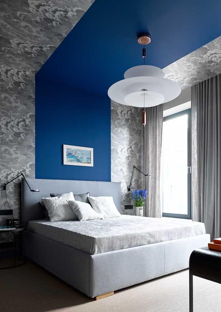 Quarto de casal masculino leva papel de parede até no teto. Uma faixa de pintura azul acompanha a linha do posicionamento da cama.