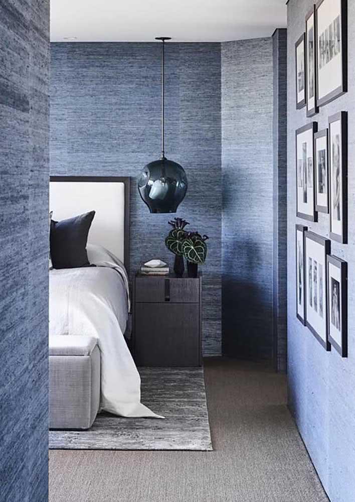 Quarto de casal com papel de parede azul por todas as paredes.
