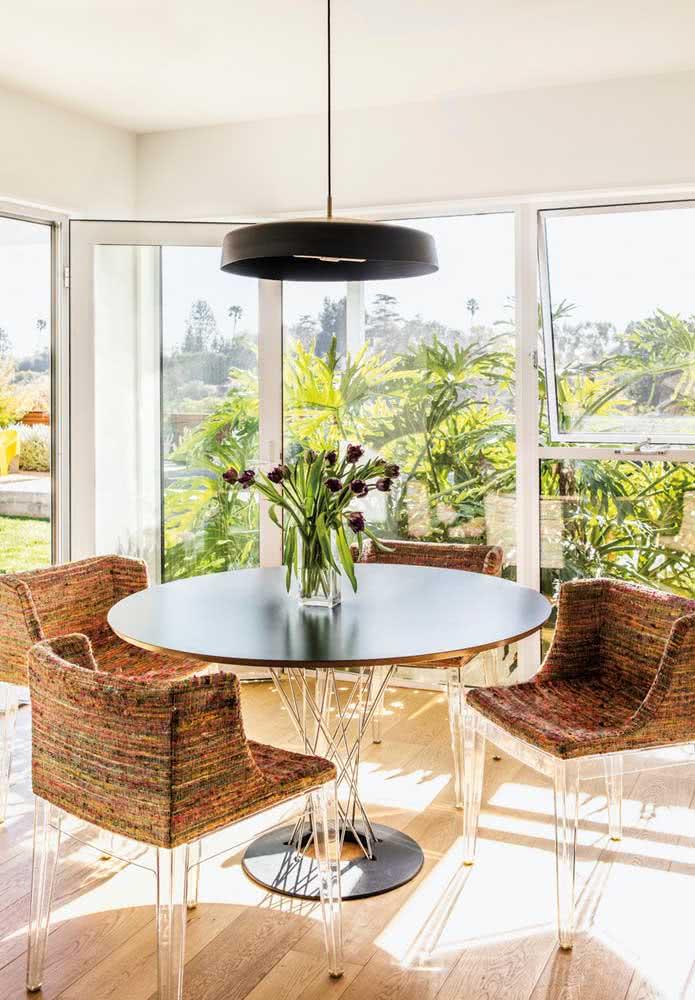Mesa redonda de metal em contraste com as cadeiras rústicas