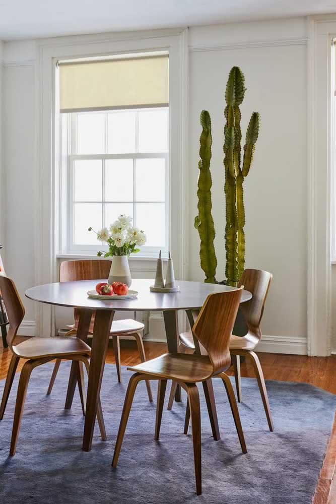 Mesa redonda de madeira com cadeiras seguindo o mesmo estilo