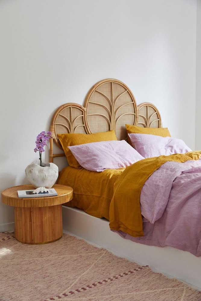 Mesa lateral redonda servindo como apoio na cabeceira da cama