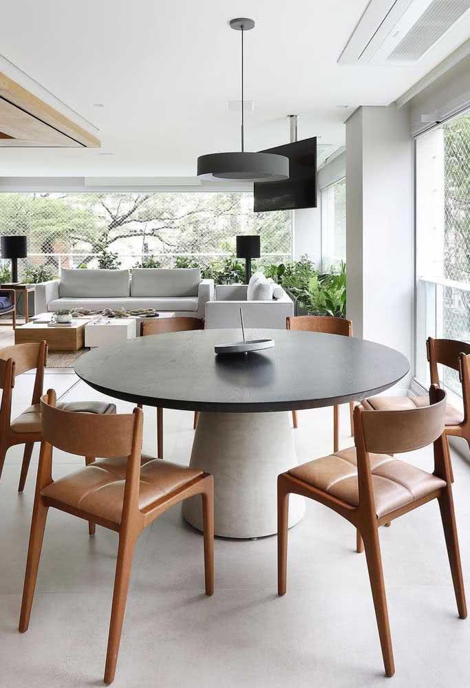 Mesa redonda preta com base de concreto e cadeiras de couro caramelo: uma composição pra lá de moderna