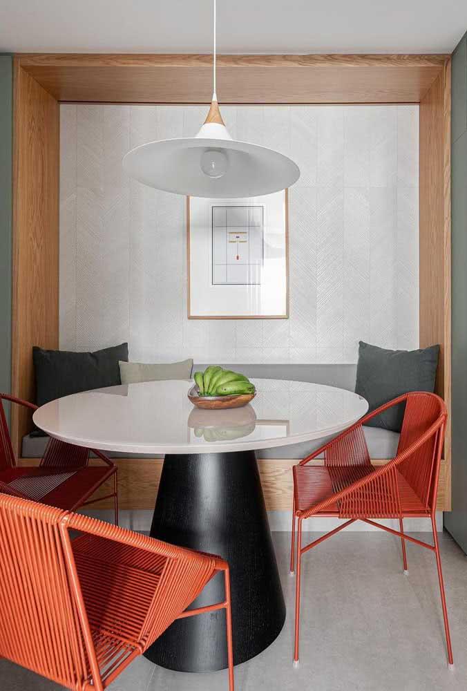 Que tal essa composição: mesa redonda branca com base preta e cadeiras laranjas