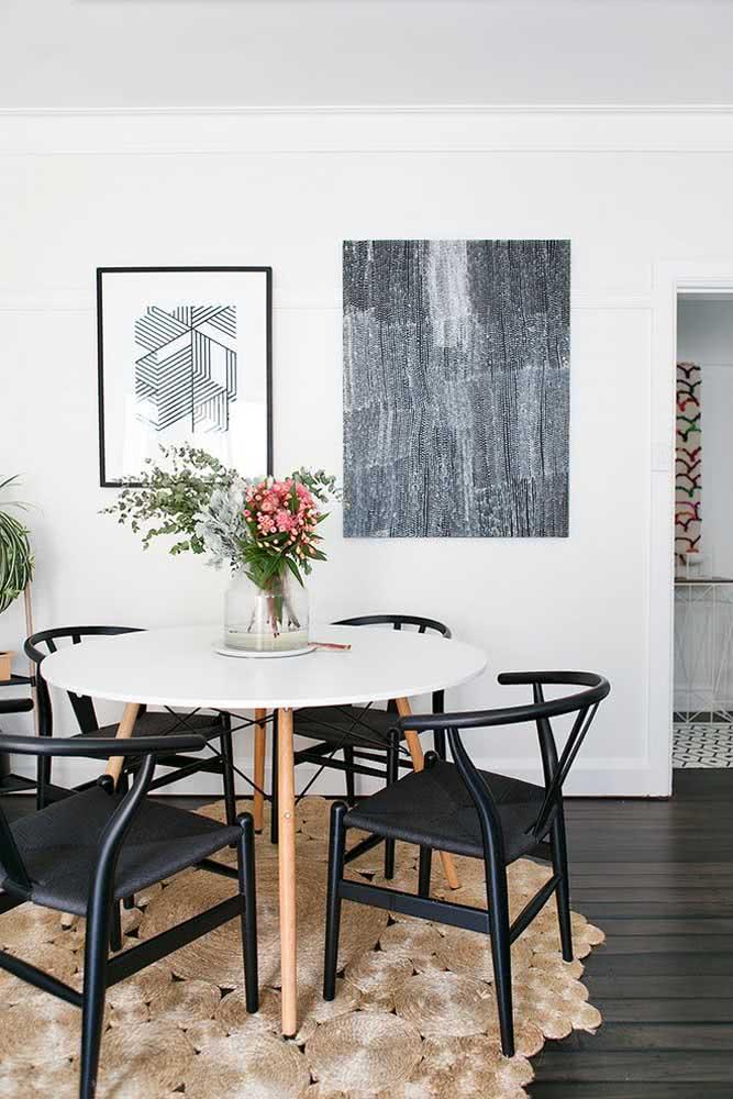 Mesa redonda branca Eames com cadeiras pretas para um formar uma composição moderna e original
