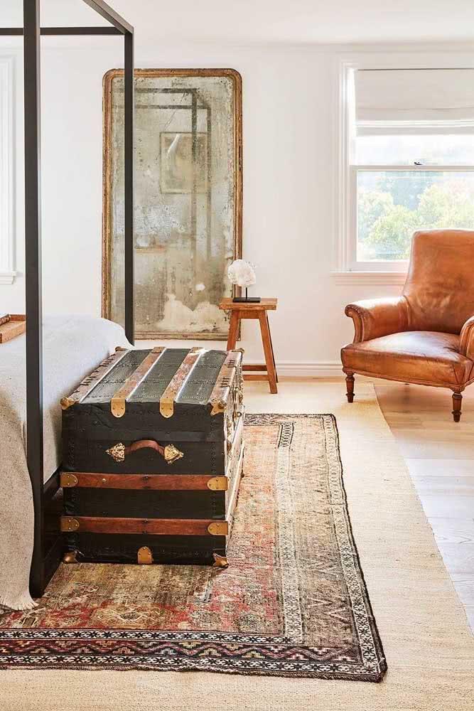 Baú verde em quarto de casal com decoração clássica e cama com dossel.