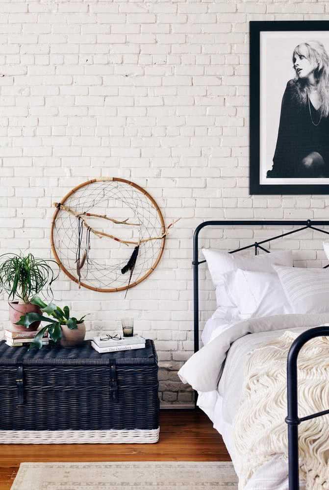 Baú de vime pintado de azul marinho e branco combinando com a estrutra metálica da cama.