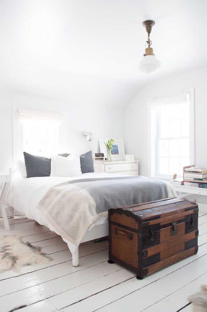 Baú de madeira com metais para quarto de casal minimalista.