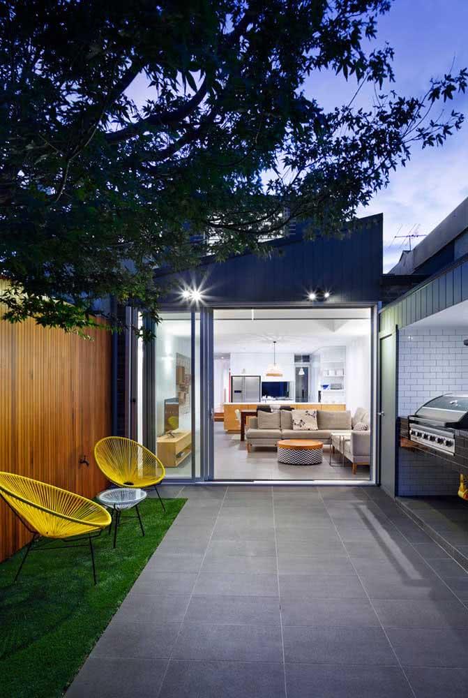 Espaço gourmet pequeno com churrasqueira e um quintal integrado à área interna da casa