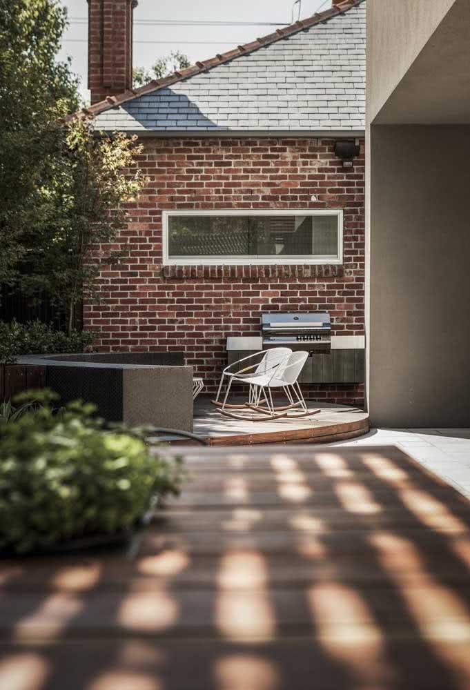 Espaço gourmet pequeno no quintal com direito a churrasqueira e cadeira de balanço
