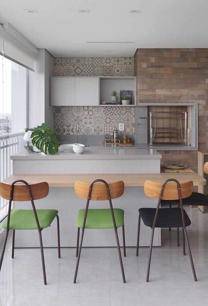Espaço gourmet pequeno de apartamento com churrasqueira e bancada para refeições