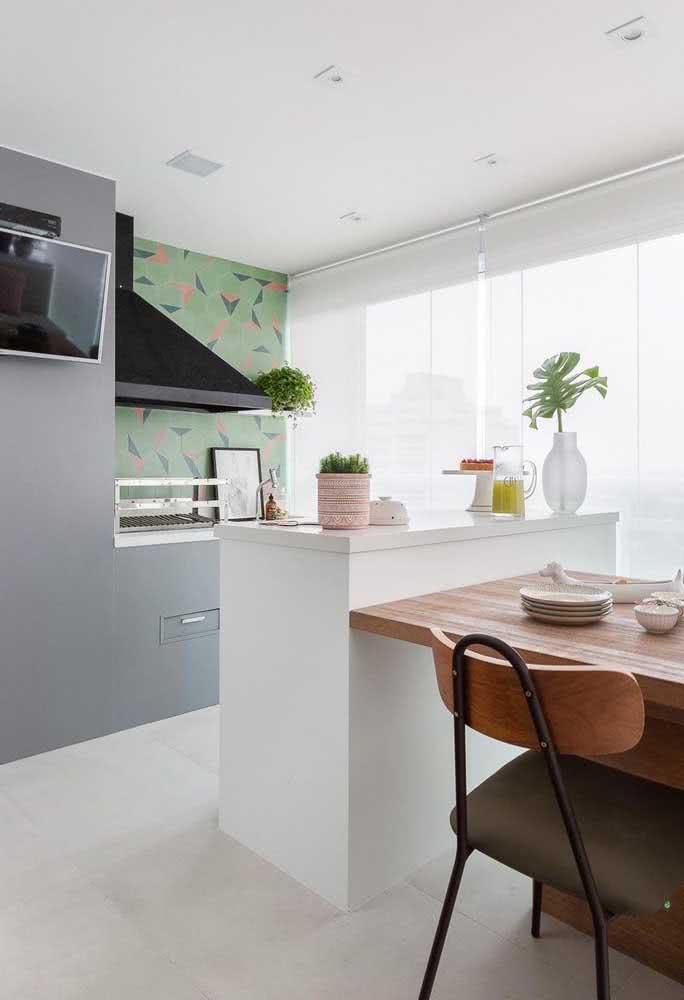 Nesse outro projeto, a mesa do espaço gourmet foi posicionada junto ao balcão