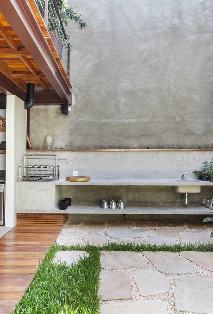 Espaço gourmet pequeno e simples com churrasqueira e bancada de concreto