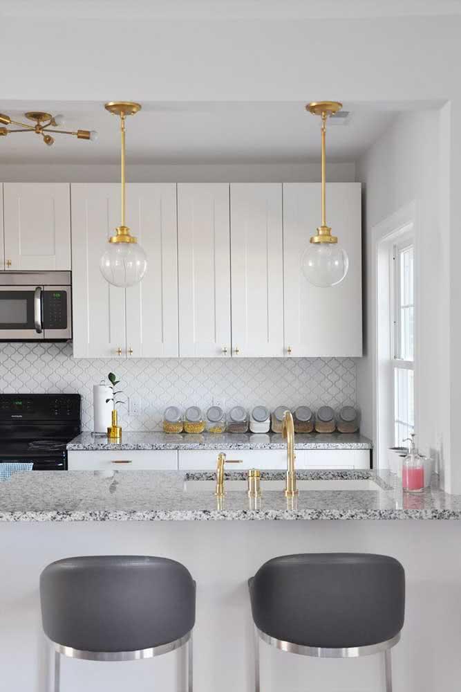 Pia de granito na cozinha acompanhada pelo balcão. Destaque para os elementos dourados que valorizaram o granito cinza