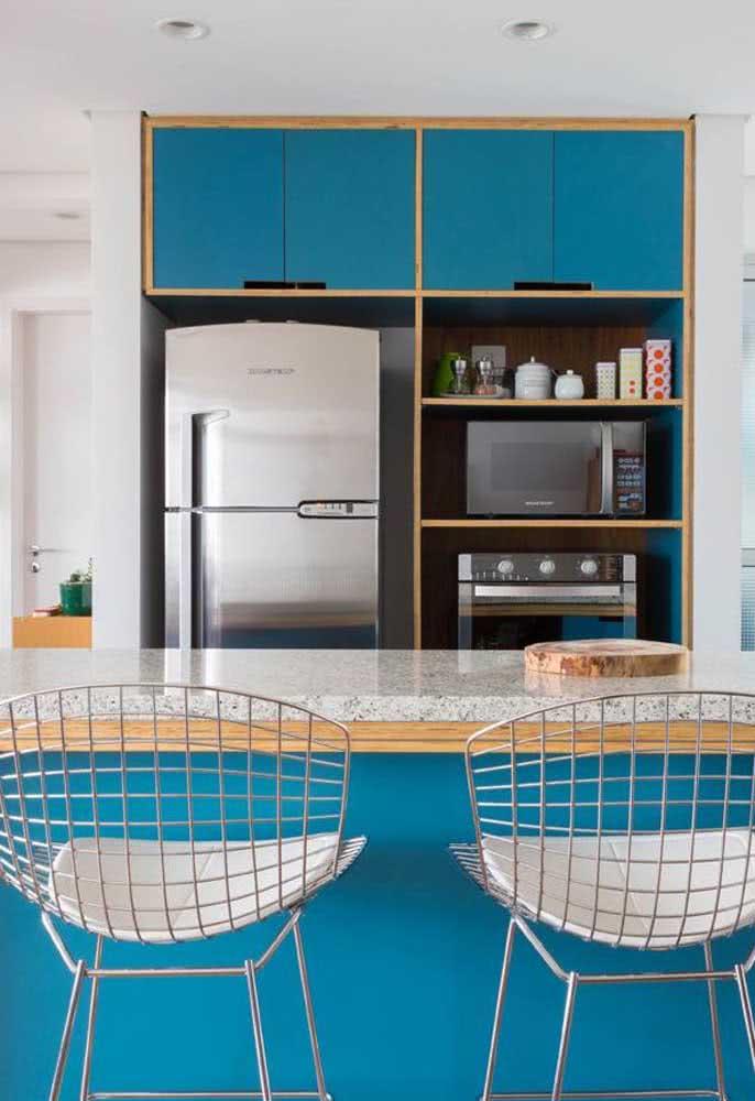 Para equilibrar o tom de azul dos armários, um balcão de granito claro na cozinha