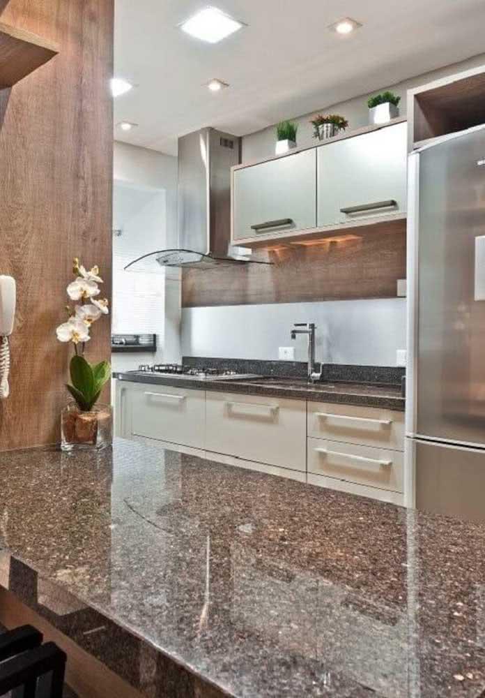 Balcão de granito na cozinha em harmonia com os detalhes em madeira