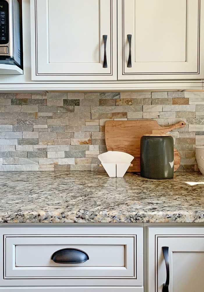 Balcão de granito na cozinha em contraste com as pedras rústicas da parede