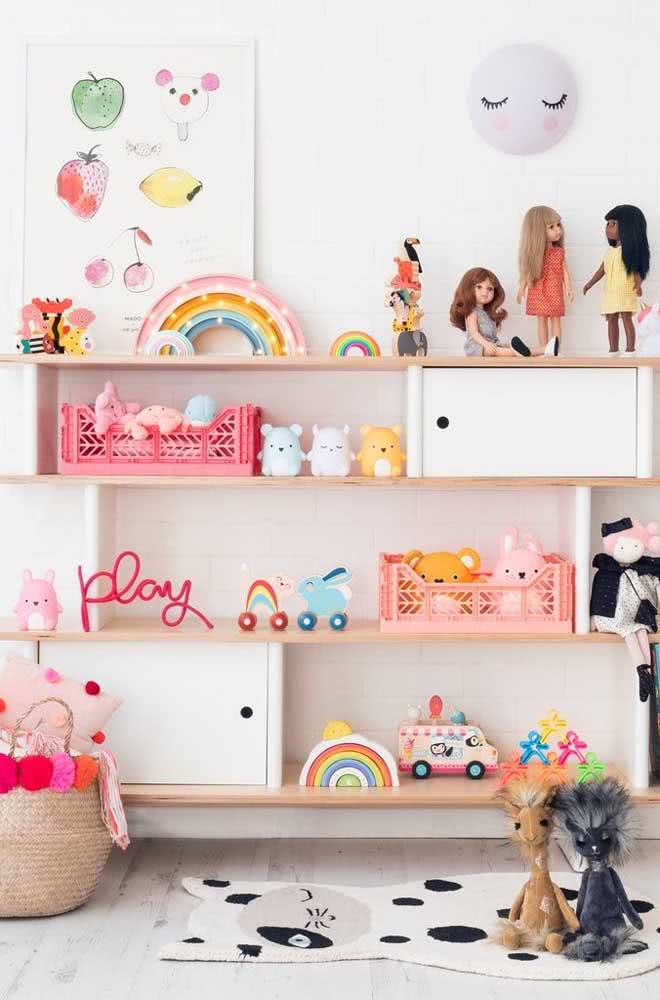 Estante para brinquedos branca, mas cheia de cor graças as bonecas e os demais brinquedos