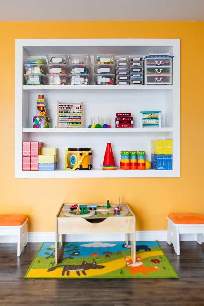 Aqui, a estante para brinquedos é um nicho na parede