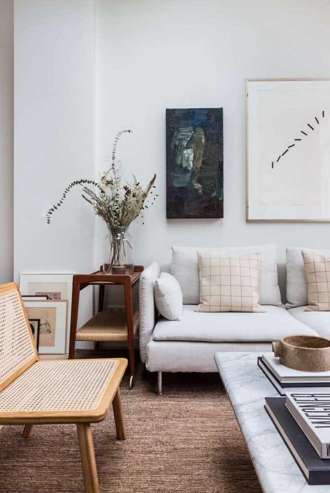 A parede branca ajuda a dar destaque a dupla de quadros clássicos para sala