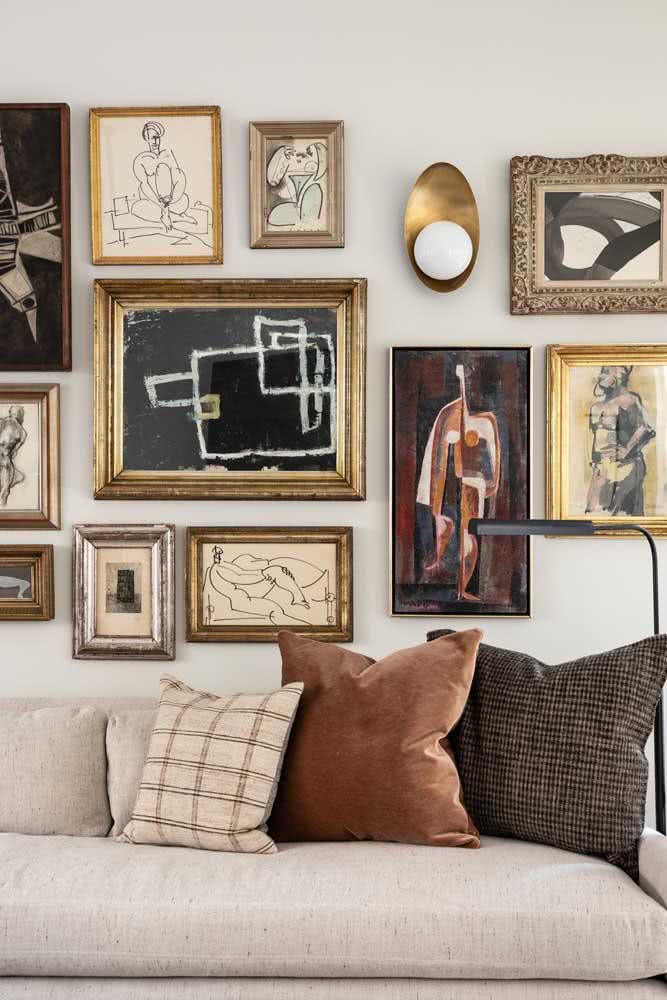 Molduras douradas para trazer equilíbrio ao conjunto de quadros clássicos