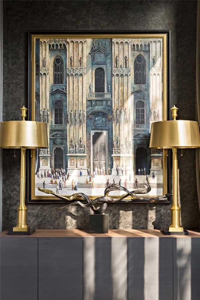 A moldura dourada do quadro clássico conversa com os abajures