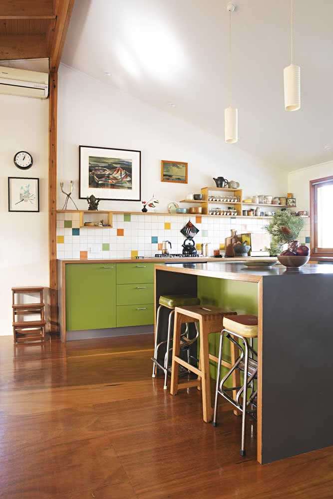 Cozinha de azulejos brancos com pequenos detalhes coloridos