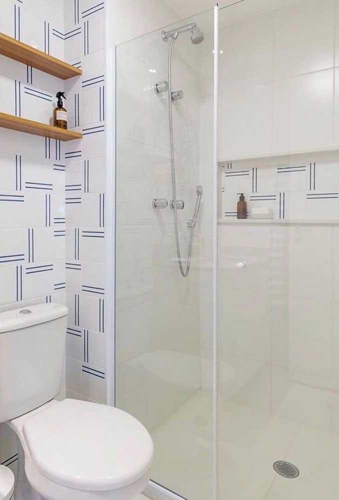 Azulejos brancos com detalhes em azul para tirar o banheiro da monocromia