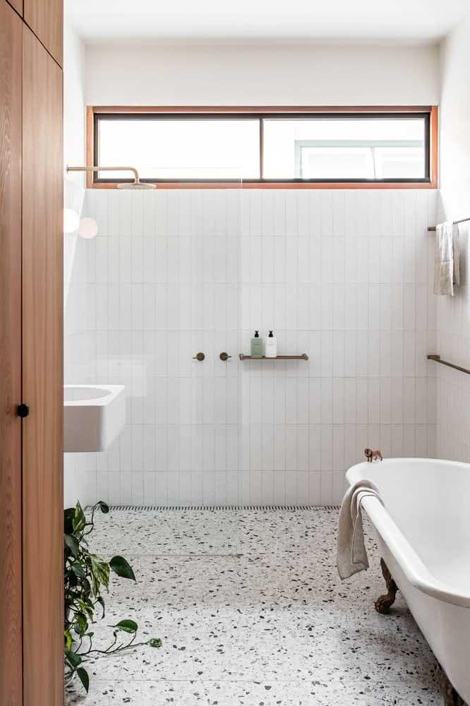 Paginação vertical para o azulejo branco do banheiro. O piso de granilite ganha destaque no ambiente