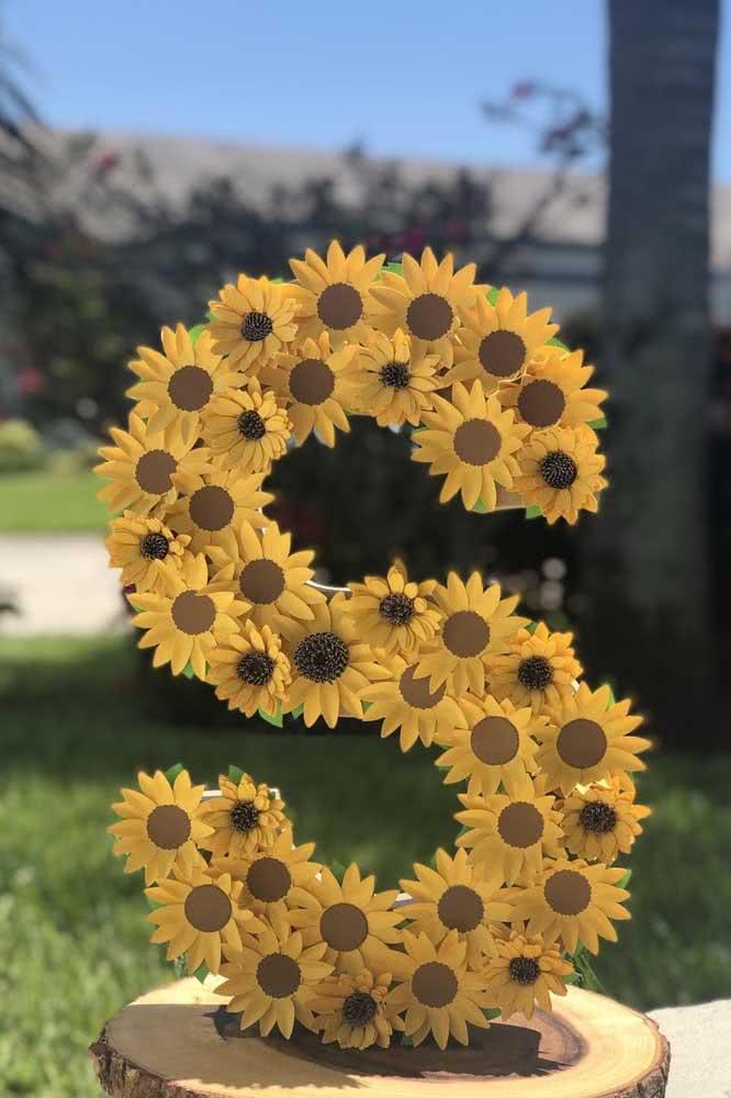 A inicial da aniversariante escrita com flores de girassol de papel
