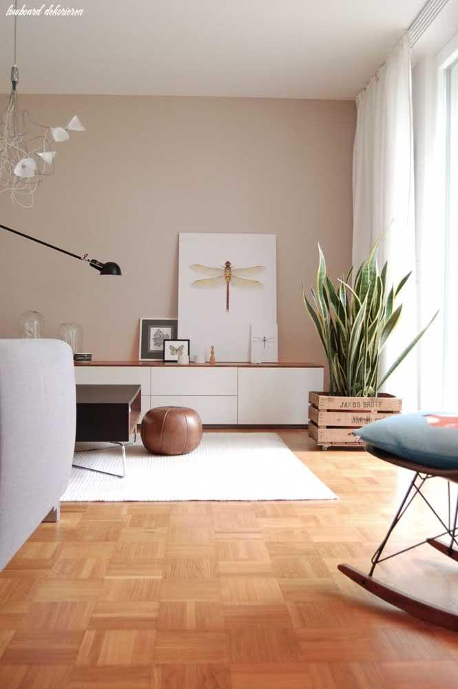 Parede nude, plantas e um piso de madeira lindo para fechar a sala com chave de ouro
