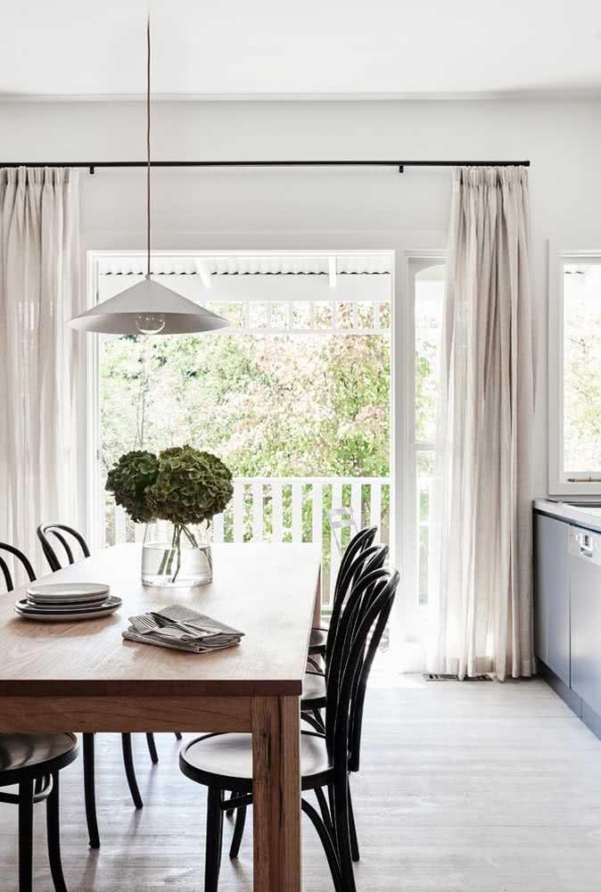 Sala de jantar nude com tons que vão do branco ao bege com o contraste marcante do preto