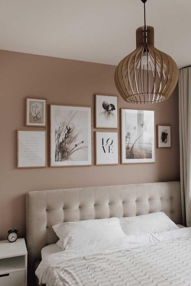 Quarto cor nude com cabeceira cinza e molduras de madeira clara. Tudo em harmonia